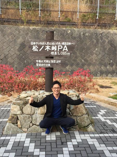 標高日本一の松の木峠PAで記念撮影するガーデンドクター柴ちゃん。