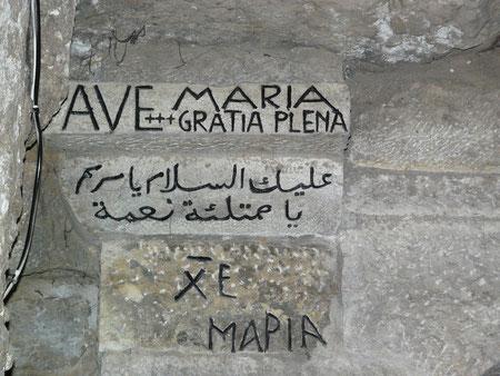 Detalle en un muro:Ave María en latín, árabe y griego