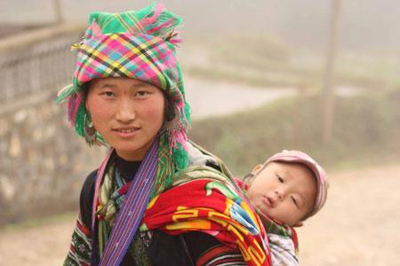 Viele der Hmong-Frauen tragen ihre kleinen Kinder auf dem Rücken