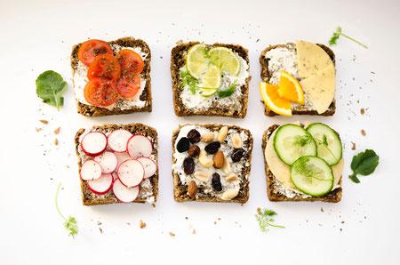 Auf dem Bild sind sechs Brote mit Frischkäse und unterschiedlicher Garnierung, wie TOmaten, Käse und Orangen, Putenbrust und Salatgurkenscheiben, Radieschen, Nüsse und Rosinen abgebildet.