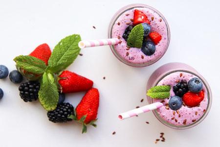 木目調のデスクの上に置かれたカレンダーと赤の目覚まし時計。