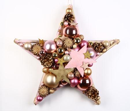 Handgefertigter Stern in rosa und gold  und mit vergoldeten Zapfen, on top Metallsternen in rosa und gold.