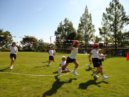 運動会で子どもたちがゴールテープを切っている写真