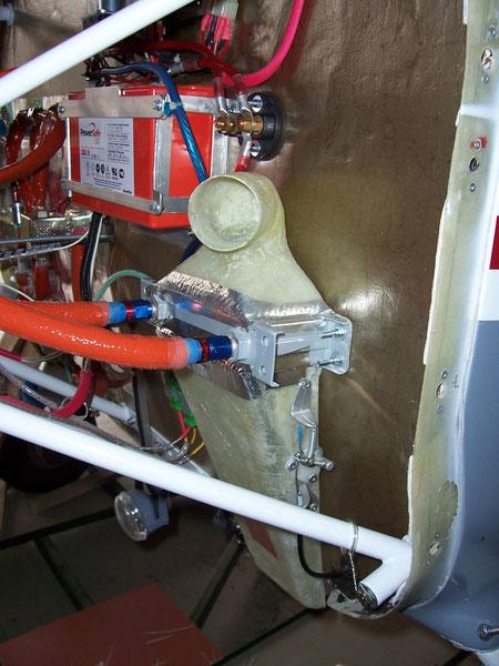Radiateur d'huile avec son divergeant d'entrée et convergent de sortie, dans lequel se trouve un clapet pour orienter l'air chaud dans l'habitacle ou vers l'extérieur
