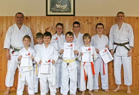 Kindertrainerin Simone Riediger (rechts) und Prüfer Sepp Neuberger (links) mit den erfolgreichen Karate-Kids.
