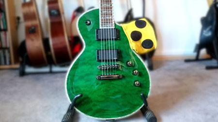 Grüne E-Gitarre in Les Paul-Bauweise, über deren Korpus eine Blindenarmbinde hängt