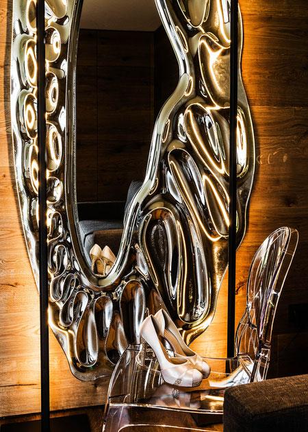 """Kontraste zum warmen Holz bilden Accessoires mit kühlem Charakter wie dieser Wandspielgel und der Stuhl  """" Ghost"""" von Kartell"""