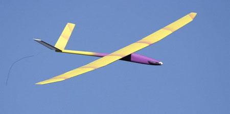 planeur radiocommandé Aldij Aeromod jaune et violet en vol, sur fond de ciel bleu