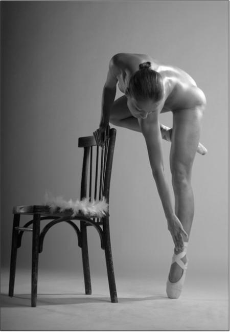 ballerina nuda appoggiata in punte con sedia