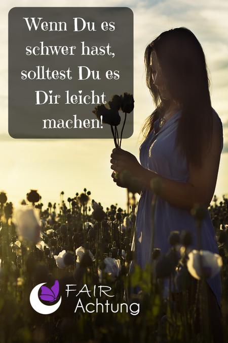 """Eine Frau steht im Wildblumenbeet und hat einige gepflückte Blumen in den Händen. Sie wirkt in sich gekehrt. Dort steht """"Wenn Du es schwer hast, solltest Du es Dir leicht machen."""""""