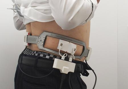 看護師から腹部にベルト型の電極を巻いてもらう