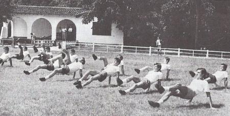 La plantilla del Villosa realizando ejercicios durante una pretemporada. Al fondo se aprecia el singular edificio que albergaba los vestuarios y el bar.