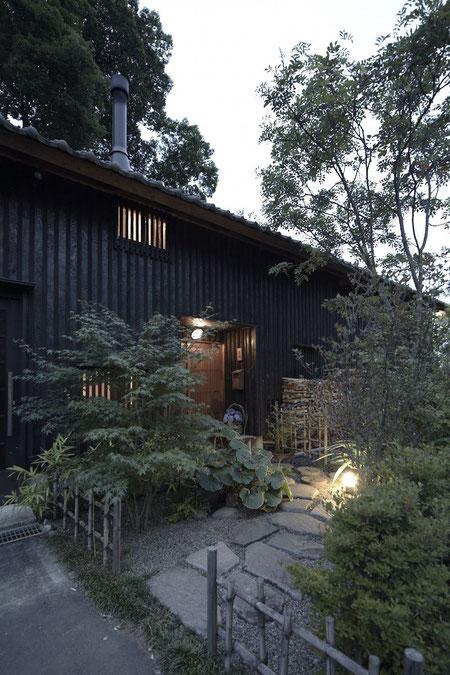 まるで旅館のような佇まいで、焼き杉の外観が美しい平屋建て。玄関を開けた時の空間の明るさを想像させる。