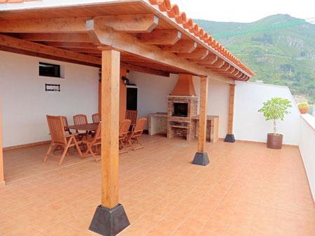 Große geflieste Terrasse mit Gartenmöbel und Grill, sowie Blick auf das Meer.