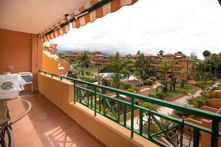 Blick von der Terrasse mit Gartenmöbel in die Grünanlage.