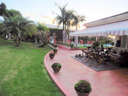Blick vom subtropischen Garten auf die Terrasse mit Holzmöbel, dem Haus und dem Pool von der Immobilie.