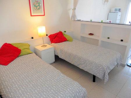 Schlafbereich im Studio mit 2 einzelnen Betten und daran schließt sich der Wohnraum an.