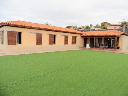 Von der großen grünen Rasenfläche vor dem Haus schaut man direkt auf die Immobilien, in in L Form gebaut wurde.