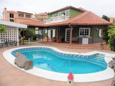 Einfamilienhaus in Naturfarben gestrichen mit einem nierenförmigen Pool vor dem Haus.