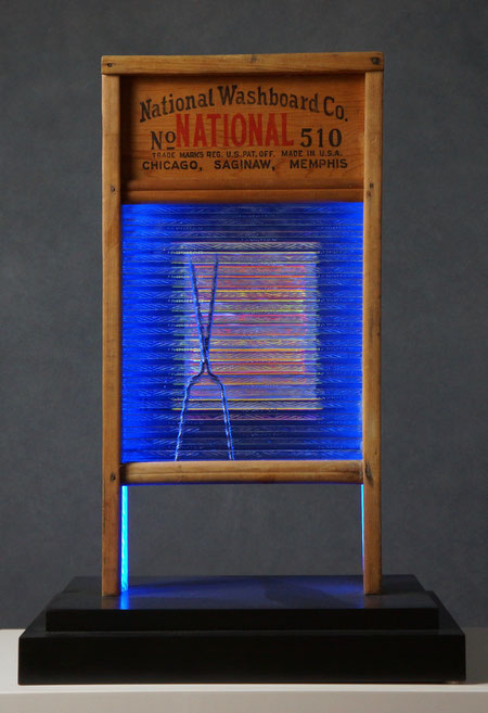 """Assemblage light art sculpture made from an old glass washboard. This sculpture acts almost as a """"light painting"""" with plexiglass, lenticular plastic, and LEDs placed in back.  The glass which refracts the light and the appearance of these components."""