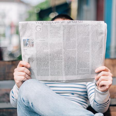 Adoptie in de media, man leest krant.