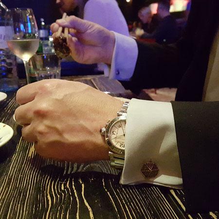 Ausgefallene Manschettenknöpfe an einer Hand mit Uhr beim Essen