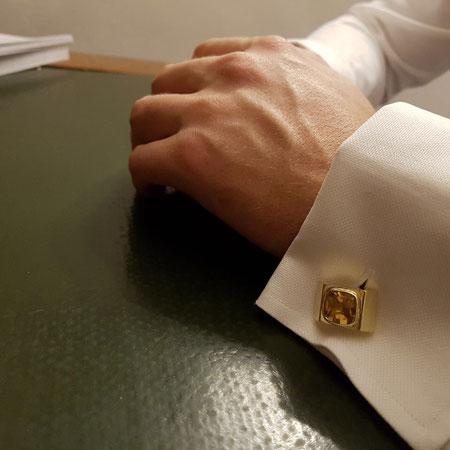 Hände mit Manschette und handgemachten Manschettenknöpfen aus Gold