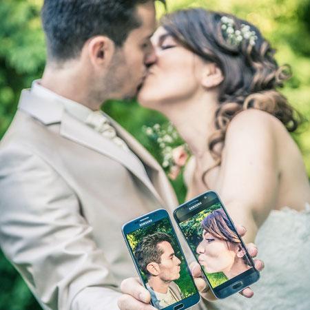 Jeunes mariés qui s'embrassent en selfie avec un portable