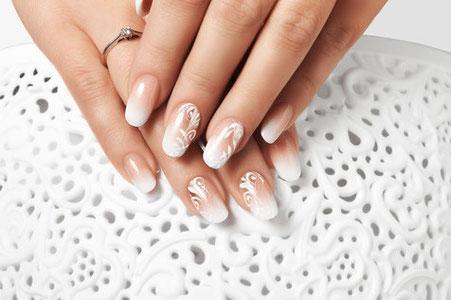 Mit weißen Ornamenten gestaltete French Nails in Nahaufnahme vor weißem Spitzendeckchen