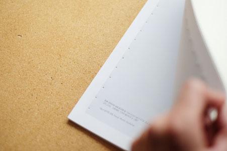 広島のイラストレーター、絵本作家の手製本で絵本を作る写真。貫通しているか確認。