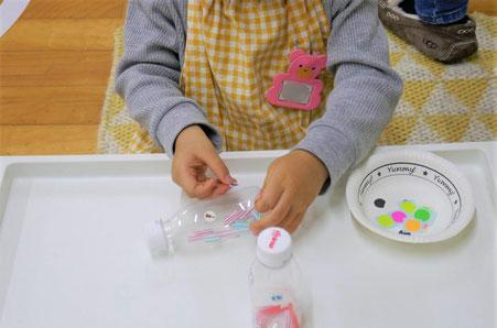 モンテッソーリの活動で、2歳児がマラカスづくりに取り組んでいます。