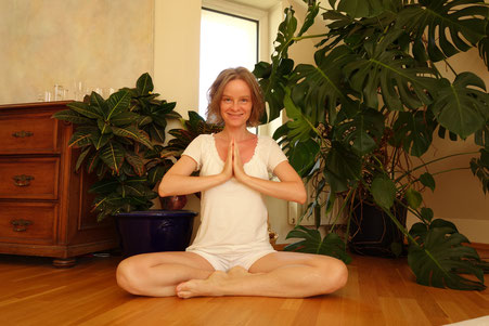junge Frau in Yogi-Haltung vor Pflanzen