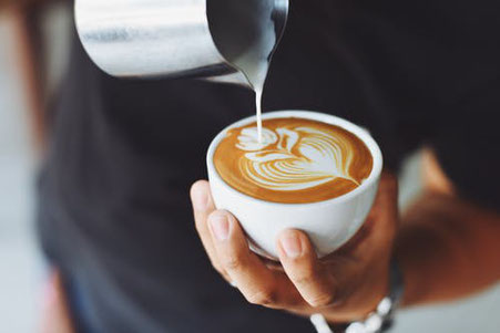 Milchschaum wird in Cappuccino Tasse gegossen