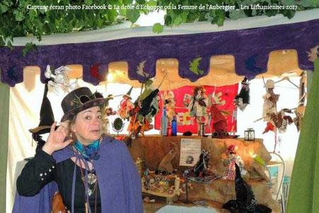 Capture d'écran d'une photo Facebook de la créatrice La femme de l'Aubergier devant son stand au Lithaniennes 2017