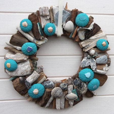 Muscheln, Holz und blaugefärbte Seeigel zum Kranz arrangier