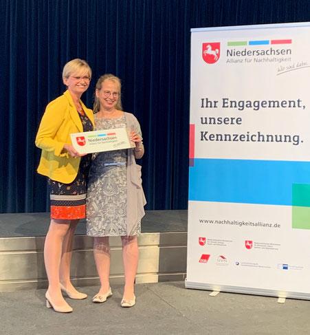 Dr. Hildegard Sander, Hauptgeschäftsführerin der Landesvertretung der Handwerkskammern Niedersachsen, überreicht die Kennzeichnung an Tanja Neumann von Heideglas Uelzen.