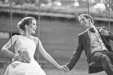 Brautpaar in Brautkleid und Anzug auf einer Gartenschaukel