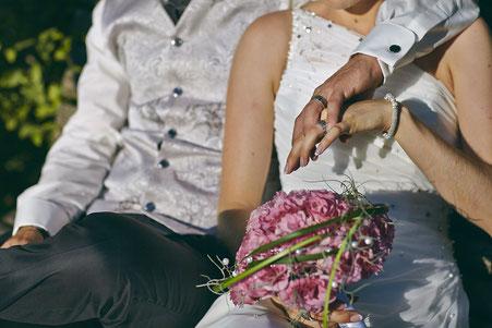 Oberkörper eines Brautpaares, welches sich umarmt und die Ringe zeigt