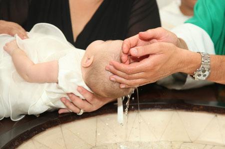 Baby wird vom Pfarrer mit Weihwasser getauft