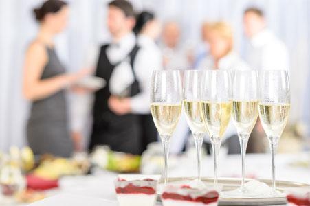 Im Vordergrund stehen Gläser mit Champagner gefüllt, im Hintergrund unterhalten sich Geschäftsleute