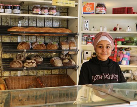 Eine Auszubildende im Fachverkauf steht an der Theke der Bäckerei und Konditorei..