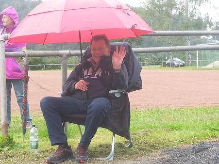 Peter Abel ein männlicher Begleiter mit Regenschutz vor dem Schützenhaus.