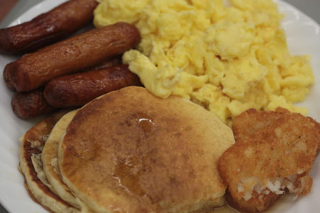 Plate of pancakes, scrambled eggs, hashbrowns and breakfast sausages.