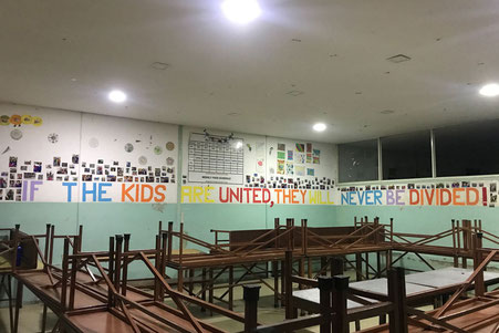 "Mit Bildern gestaltete Wand mit Spruch ""If the kids are united, they will never be divided!"""