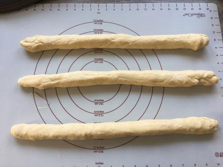 Teig auf Backmatte in drei Strängen geteilt