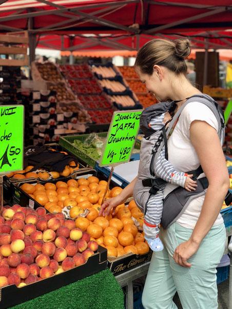 Mutter mit Baby auf Wochenmarkt am Obststand mit Mandarinen und Pfirsichen, frisches Obst