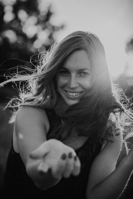Frau streckt lächelnd ihre Hand in Richtung des Betrachters