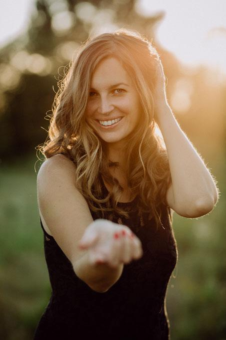 Porträt einer jungen Frau in der untergehenden Sonne