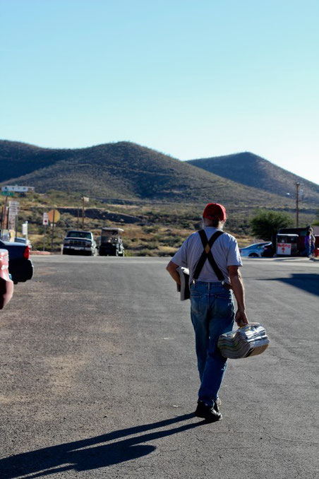 Old man walking towards distance carrying newspapers end of the day on a road in arizona