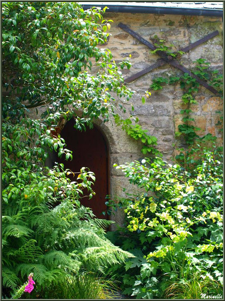 Le Manoir : un bâtiment annexe à l'entrée avec une ses portes dans un écrin de végétation - Les Jardins du Kerdalo à Trédarzec, Côtes d'Armor (22)
